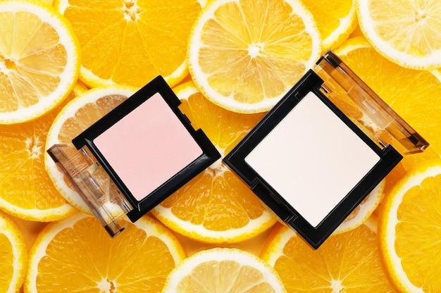 Widok z góry na puder i rozświetlacz. produkt kosmetyczny do skóry twarzy. koncepcja maquillage, kosmetyczna i wizażowa. miejsce na tekst lub projekt, układ płaski. pyszne plastry pomarańczy i cytryny na tle.