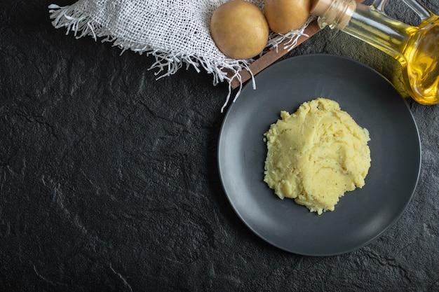 Widok z góry na puree i świeże ziemniaki. puree ziemniaczane na czarnym talerzu.