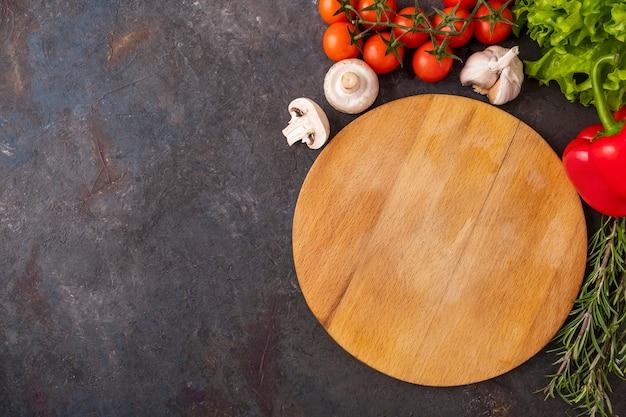 Widok z góry na pustą drewnianą deskę do krojenia i warzywa. przestrzeń tekstowa