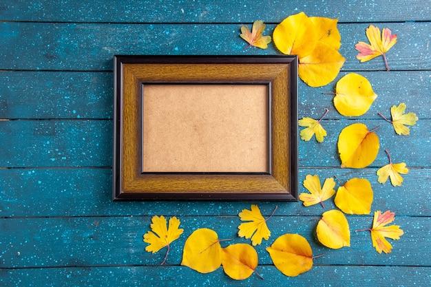 Widok z góry na pustą drewnianą ramkę na zdjęcia i żółte liście w różnych rozmiarach na niebieskim tle