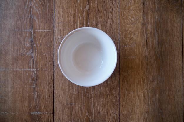 Widok z góry na pustą miskę biały na tle drewnianych