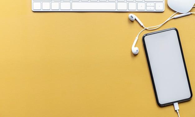 Widok z góry na pusty ekran smartfona z białą klawiaturą i myszą na żółtym tle.
