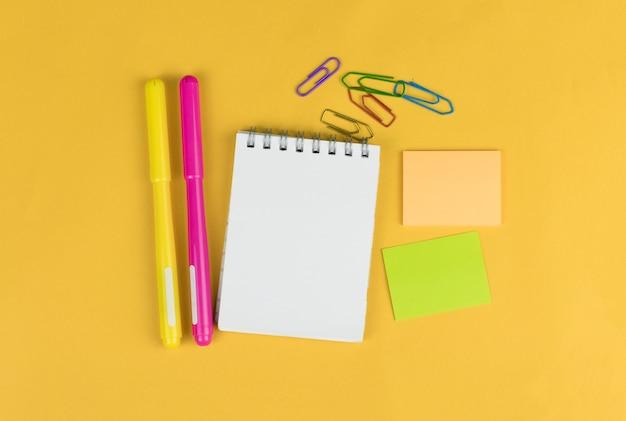 Widok z góry na pusty notatnik i przybory szkolne, takie jak kolorowe markery, naklejki i clipery na żółtym tle, miejsce na tekst.