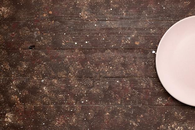 Widok z góry na pusty różowy talerz na brązowym rustykalnym, drewnianym talerzu oolor
