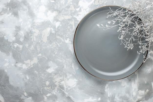 Widok z góry na pusty szary talerz na białym, talerzowym biurku ze sztućcami,