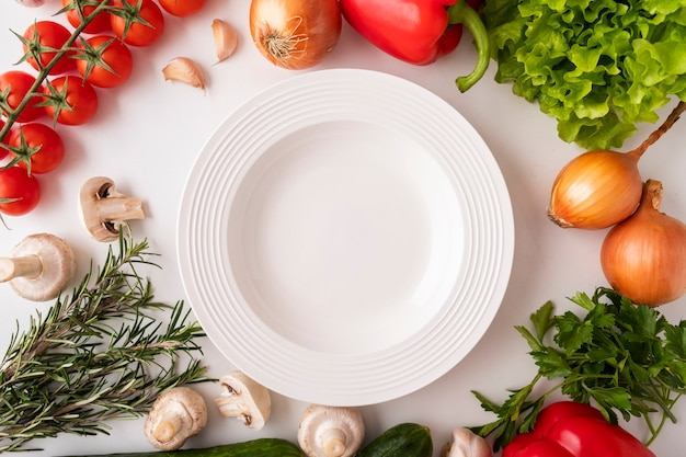 Widok z góry na pusty talerz, surowe warzywa i przyprawy. koncepcja gotowania i wegetariańskie. zdrowe jedzenie. widok z góry.