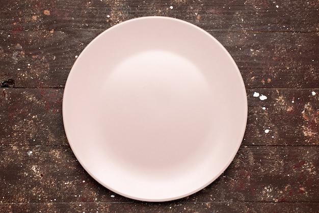 Widok z góry na pusty talerz zaróżowiony na brązowym, rustykalnym, drewnianym talerzu