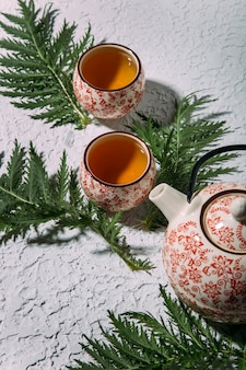 Widok z góry na pyszną herbatę ziołową na białym betonowym tle