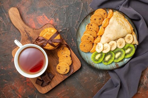 Widok z góry na pyszną krepę posiekane ciasteczka z owocami cytrusowymi na ciemnym ręczniku i tabliczkę czekolady filiżankę czarnej herbaty w mieszanym kolorze