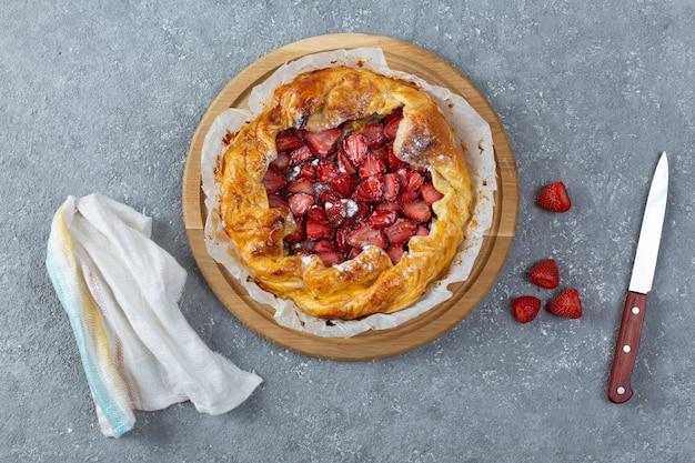 Widok z góry na pyszną pieczoną tartę z truskawkami, nożem i ściereczką kuchenną na jasnoszarym tle
