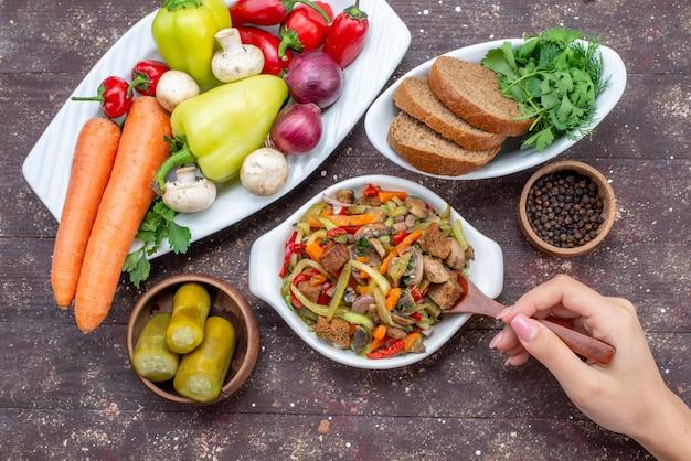 Widok z góry na pyszną sałatkę mięsną z pokrojonym mięsem i gotowanymi warzywami oraz pieczywo piklowe na brązowym, danie z mięsa