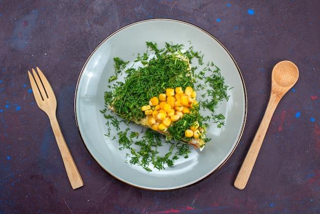 Widok z góry na pyszną sałatkę z majonezu, kukurydzy i kurczaka wewnątrz talerza na ciemnym biurku.
