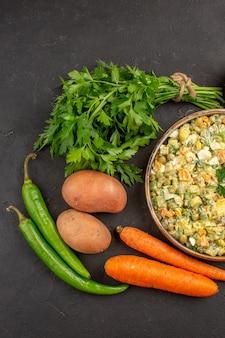 Widok z góry na pyszną sałatkę ze świeżych warzyw na ciemnej powierzchni