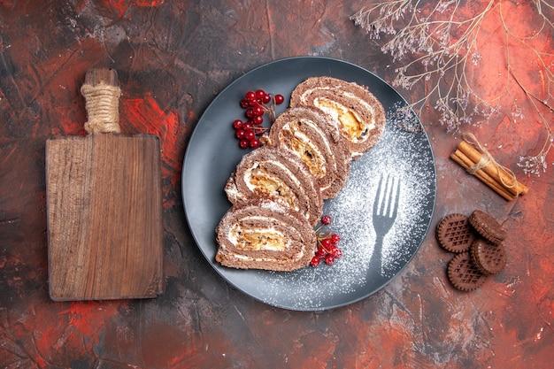 Widok z góry na pyszne bułki biszkoptowe z ciasteczkami na ciemnej powierzchni