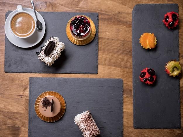 Widok z góry na pyszne ciasta o różnych smakach i kolorach na drewnianym stole. smaczne desery. świeże desery. pyszna filiżanka kawy. różne ciasto budyniowe.