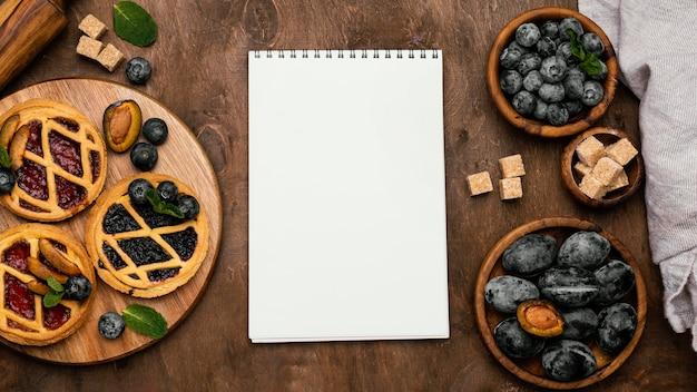 Widok z góry na pyszne ciasta owocowe ze śliwkami i notatnikiem