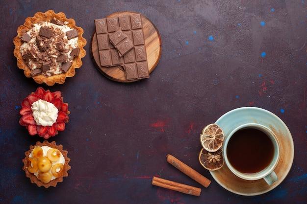 Widok z góry na pyszne ciasta z kremową czekoladą i owocami z herbatą na ciemnej powierzchni