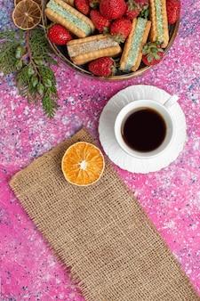 Widok z góry na pyszne ciasteczka waflowe ze świeżymi czerwonymi truskawkami i filiżanką herbaty na różowej powierzchni