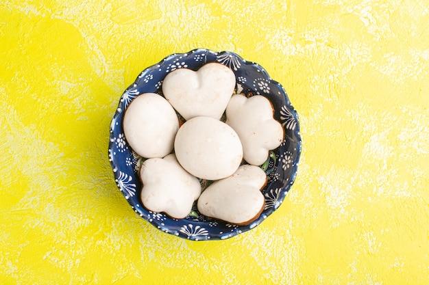 Widok z góry na pyszne ciasteczka wewnątrz płyty na żółtej podłodze