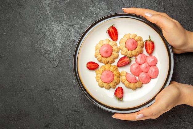 Widok z góry na pyszne ciasteczka z różowym kremem wewnątrz talerza na szarej powierzchni