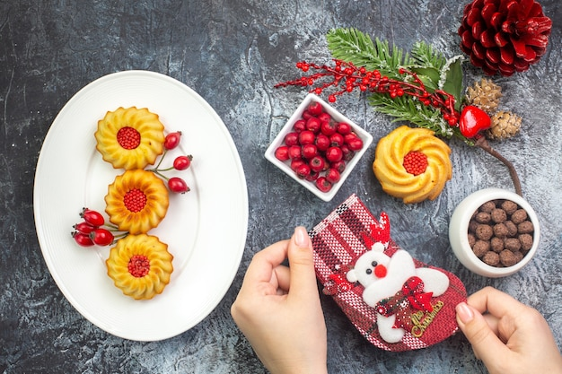 Widok z góry na pyszne ciastka i dereń na białym talerzu noworoczna skarpeta z czerwonego stożka iglastego na ciemnej powierzchni