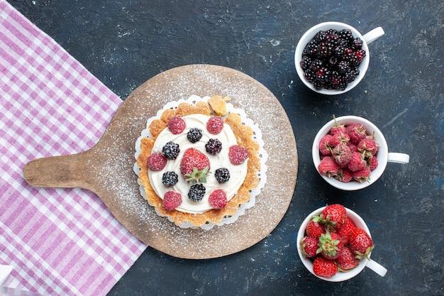 Widok z góry na pyszne ciastko z kremem cukrowym w proszku i jagodami wraz z filiżankami jagód na ciemnym biurku, ciastko jagodowo-owocowe