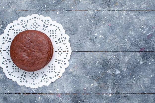 Widok z góry na pyszne ciasto czekoladowe okrągłe utworzone na białym tle na szarym biurku, piec czekoladowe ciasto kakaowe słodkie herbatniki