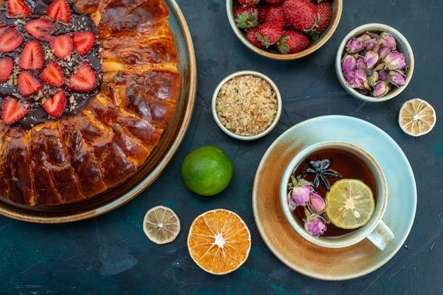 Widok z góry na pyszne ciasto truskawkowe pieczone pyszne ciasto z filiżanką herbaty na ciemnoniebieskiej powierzchni