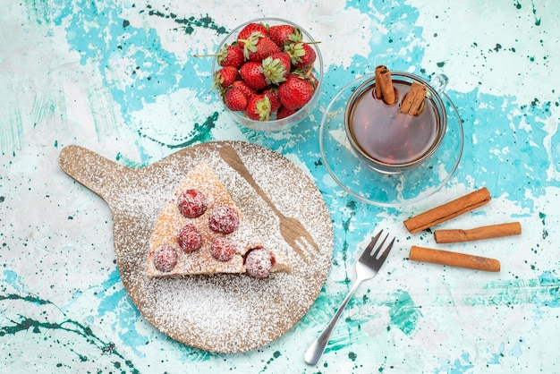 Widok z góry na pyszne ciasto truskawkowe pokrojone w plastry pyszne ciasto cukrowe w proszku z herbatą na jasnoniebieskim, jagodowym cieście słodkie ciasto do pieczenia