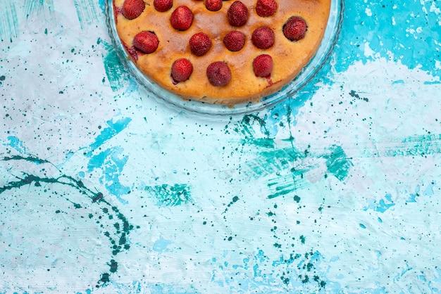 Widok z góry na pyszne ciasto truskawkowe w kształcie okrągłym z owocami na wierzchu na jasnoniebieskim, ciastowym, słodkim ciastku owocowym