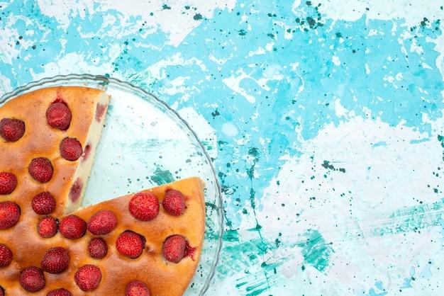 Widok z góry na pyszne ciasto truskawkowe w plasterkach i całe pyszne ciasto na jasnoniebieskim, jagodowym słodkim cieście do pieczenia