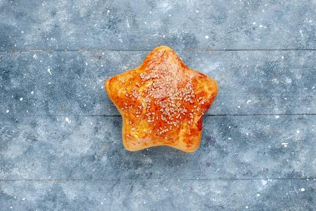 Widok z góry na pyszne ciasto w kształcie gwiazdy na szarym, słodkim ciastku z ciasta cukrowego