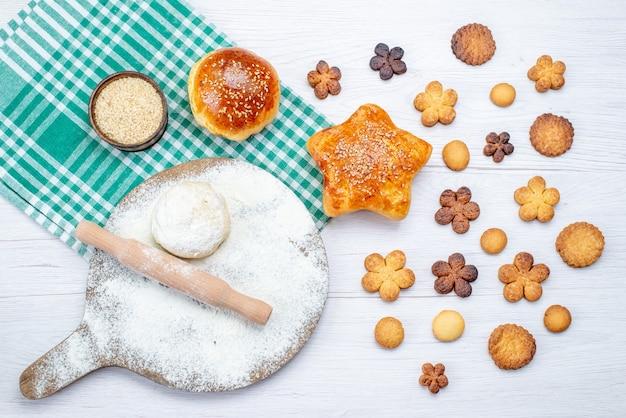 Widok z góry na pyszne ciasto wraz z ciasteczkami i surowym ciastem na lekkim biurku, ciastko biszkoptowe, słodki cukier