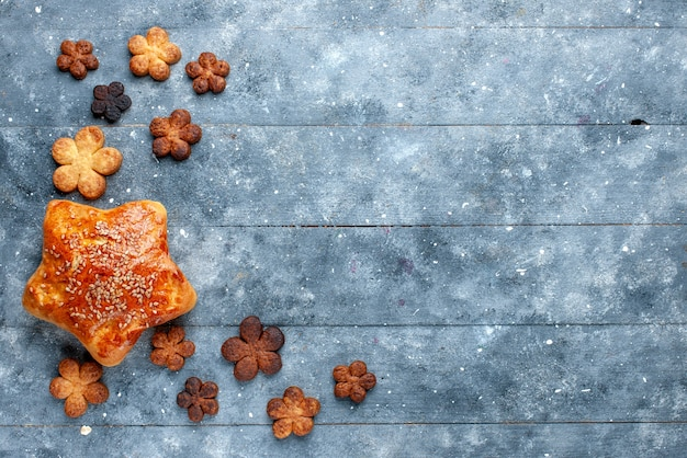 Widok z góry na pyszne ciasto wraz z pysznymi ciasteczkami na szarym, słodkim cukierniczym cieście do pieczenia