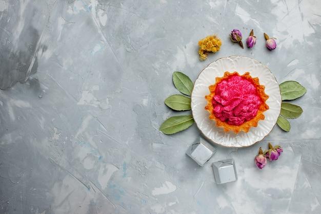 Widok z góry na pyszne ciasto z różową śmietaną i czekoladkami na lekkim, słodkim kremem do pieczenia ciast biszkoptowych