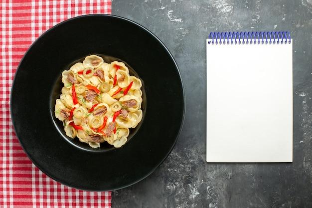 Widok z góry na pyszne conchiglie z warzywami i zielenią na talerzu i nożu na czerwonym ręczniku w paski obok notatnika na szarym tle