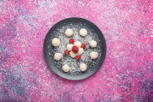 Widok z góry na pyszne cukierki kokosowe słodkie kulki na jasnoróżowej powierzchni