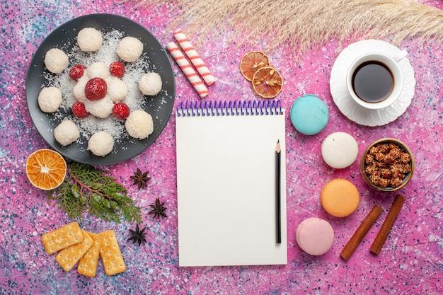 Widok z góry na pyszne cukierki kokosowe z makaronikami i filiżanką herbaty na jasnoróżowej powierzchni