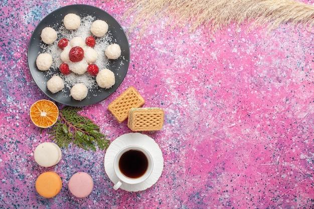 Widok z góry na pyszne cukierki kokosowe ze świeżymi czerwonymi truskawkami i goframi na różowej powierzchni