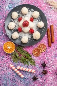Widok z góry na pyszne cukierki kokosowe ze świeżymi czerwonymi truskawkami na różowej powierzchni