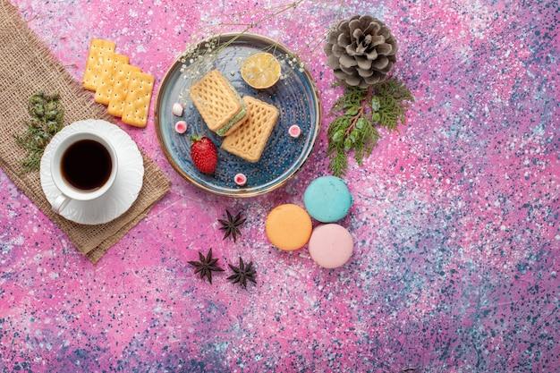 Widok z góry na pyszne gofry z filiżanką herbaty i makaronikami na różowej powierzchni