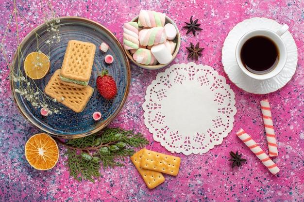 Widok z góry na pyszne gofry z filiżanką herbaty i ptasie mleczko na jasnoróżowej powierzchni