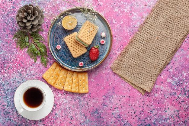 Widok z góry na pyszne gofry z francuskimi krakersami macarons i herbatą na różowej powierzchni