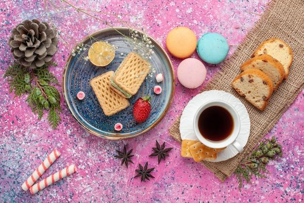 Widok z góry na pyszne gofry z francuskimi makaronikami i herbatą na różowej powierzchni