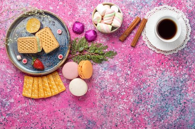 Widok z góry na pyszne gofry z makaronikami i filiżanką herbaty na różowej powierzchni