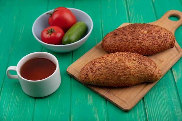 Widok z góry na pyszne i sezamowe paszteciki na drewnianej desce kuchennej z filiżanką herbaty z warzywami na misce na zielonym drewnianym tle