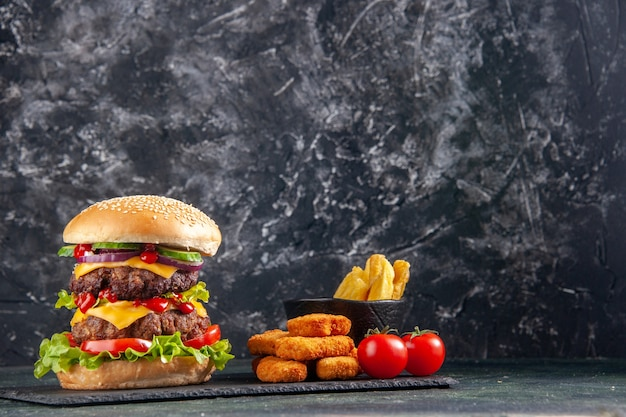 Widok z góry na pyszne kanapki na tacy ciemnego koloru i frytki z kurczaka bryłki pomidorów na czarnej powierzchni