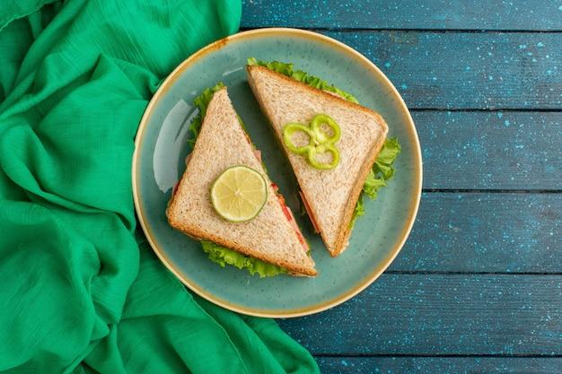 Widok z góry na pyszne kanapki wewnątrz niebieskiego talerza na niebieskim biurku