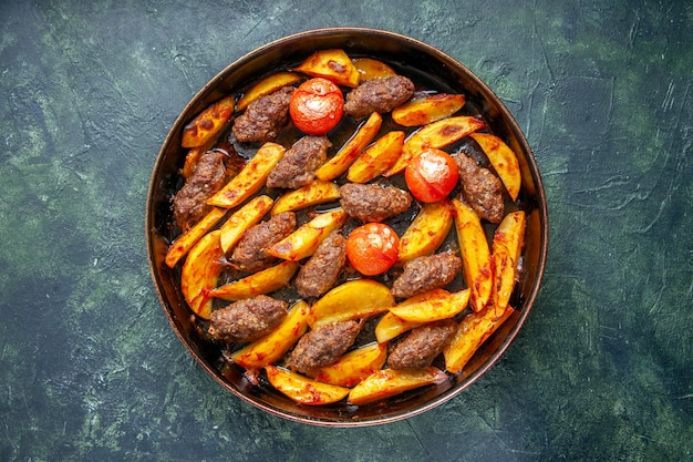 Widok z góry na pyszne kotlety mięsne zapiekane z ziemniakami i pomidorami na zielonym i czarnym mieszanym tle