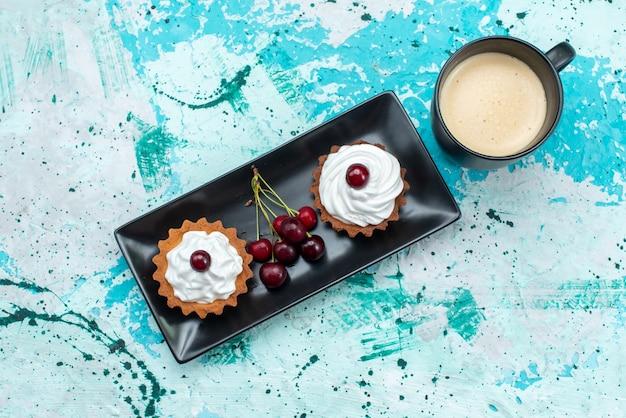 Widok z góry na pyszne kremowe ciasta ze świeżymi wiśniami na jasnoniebieskim, kremowym biszkopcie na słodko